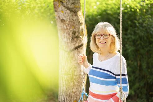 Happy woman sitting on swing in garden - AKLF00038