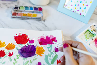 Woman painting botanic plants and flowers with watercolor on paper - GEMF04668