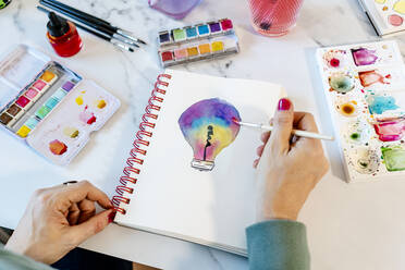 Woman painting light bulb with watercolors on spiral notebook at table - GEMF04671