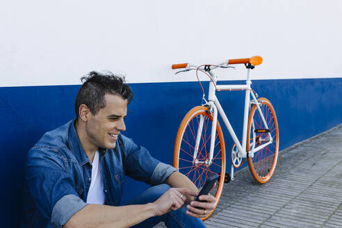 Smiling handsome man using mobile phone by bicycle against wall - XLGF01193