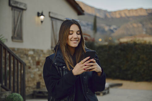 Smiling beautiful woman using mobile phone by house - ACPF01143