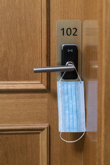Protective face mask hanging on door lock - AKLF00063
