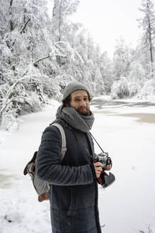 Young man with camera smiling while standing in forest - VPIF03561