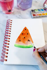 Woman painting watermelon slice with watercolor in book - GEMF04687