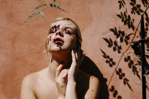 Woman with leaves shadow on face while standing against wall - TCEF01528