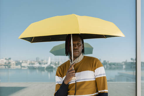Man holding yellow umbrella while standing against glass wall - EGAF01817