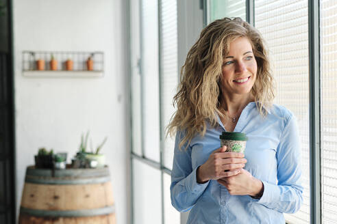 Smiling blond woman with reusable cup looking through window - AGOF00052