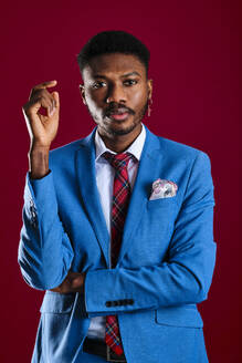 Fashionable man wearing blue suit against red background - AGOF00055