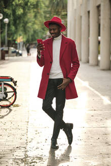 African fashionable man using smart phone while standing on footpath - AGOF00070