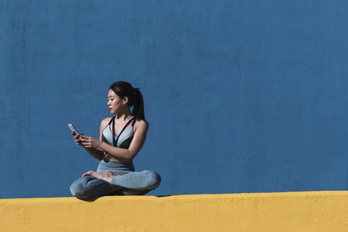 Woman using mobile phone while sitting cross legged against blue wall - PNAF00678