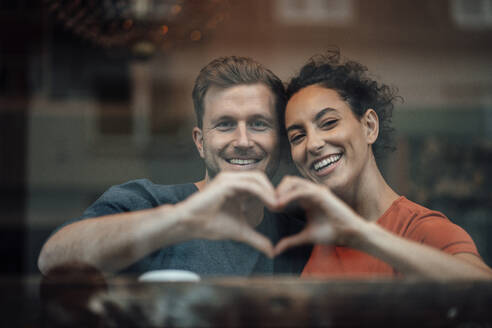 Smiling couple making heart with hand while sitting by cafe window - JOSEF03517