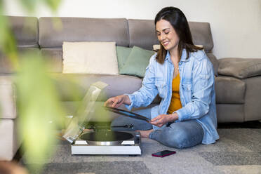 Smiling woman with turntable holding record while sitting by sofa at home - AFVF08198