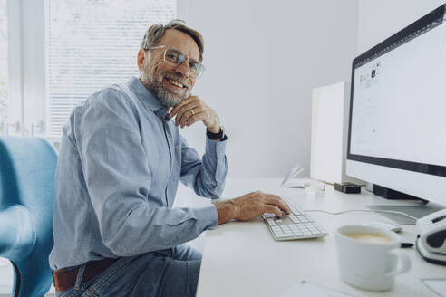 Smiling mature businessman working at home office - MFF07207