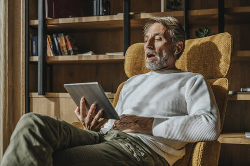 Man talking on video conference through digital tablet while sitting at home - MFF07274