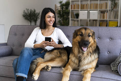 Happy woman with smart phone looking away while sitting with dog on sofa at home - GIOF11306