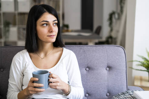 Thoughtful young woman with coffee cup in living room looking away - GIOF11321