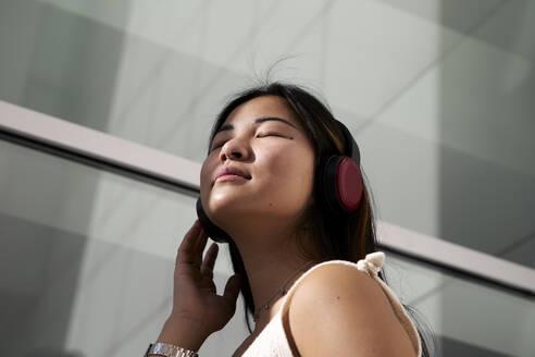 Asian woman listening music through headphones outdoors - VEGF03944