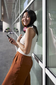 Happy woman with smart phone leaning on glass wall - VEGF03947