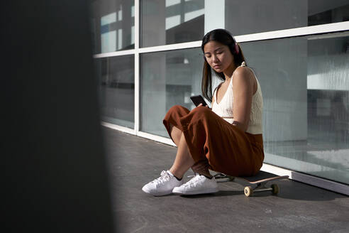 Asian woman using smart phone while sitting on skateboard during sunny day - VEGF03950
