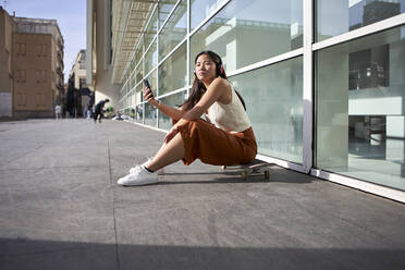 Woman with mobile phone sitting on skateboard during sunny day - VEGF03953