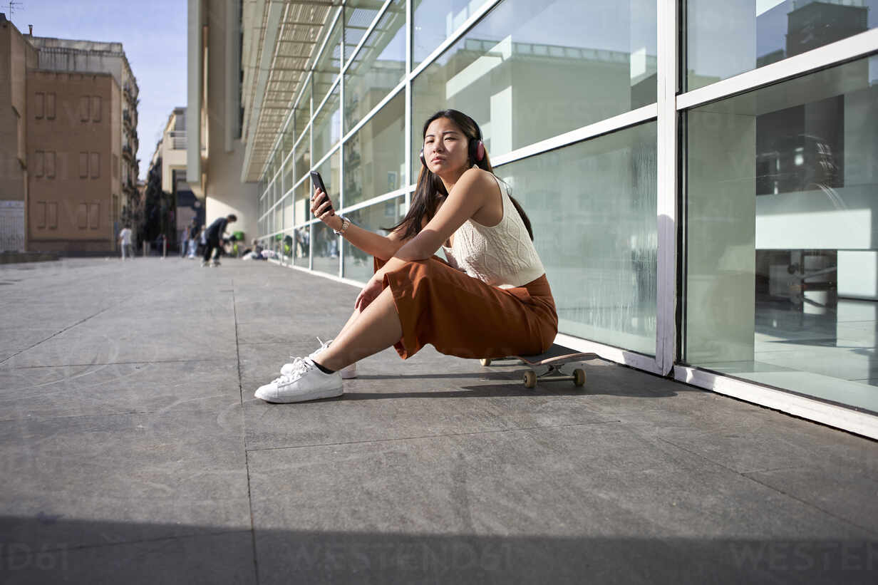 Woman with mobile phone sitting on skateboard during sunny day - VEGF03953 - Veam/Westend61
