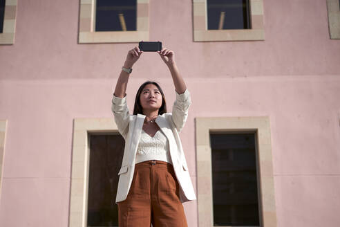 Stylish woman taking selfie on smart phone against building - VEGF03959