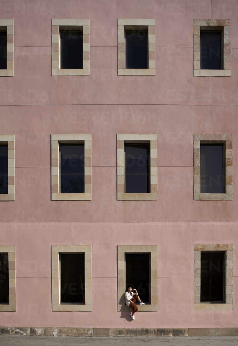 Frau sitzt auf dem Fensterbrett eines Gebäudes - VEGF03962 - Veam/Westend61
