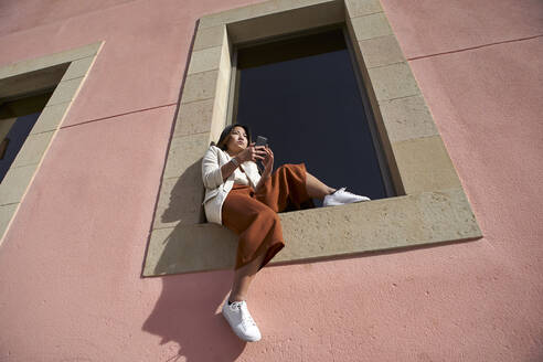 Young woman with smart phone sitting on window sill of building - VEGF03965