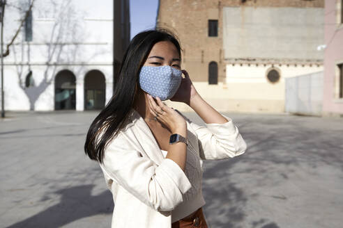 Young woman with protective face mask on footpath during sunny day - VEGF03968
