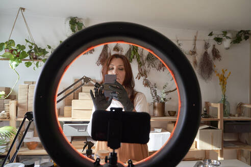 Mature female influencer preparing ring light and smart phone for video tutorial at workshop - VEGF03974
