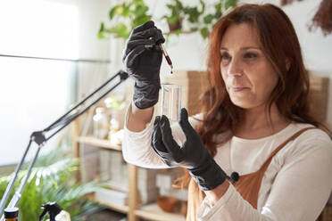 Mature woman holding oil bottle at workshop - VEGF03980