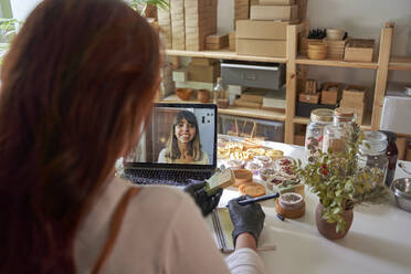Female influencer writing in note pad while talking with customer on video call through laptop at workshop - VEGF03983