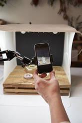 Female entrepreneur's hand photographing handmade soap at workshop - VEGF04004