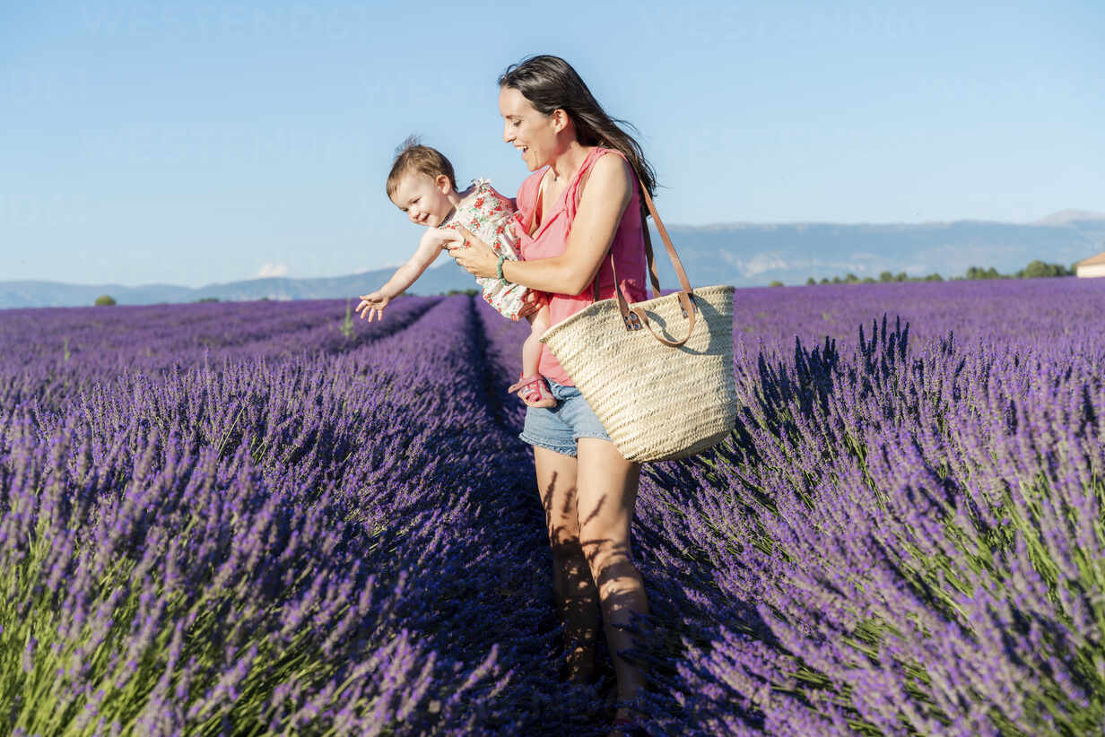 Mother holding happy baby girl in a lavender field at afternoon in Valensole, Provence, France - GEMF04694 - Gemma Ferrando/Westend61