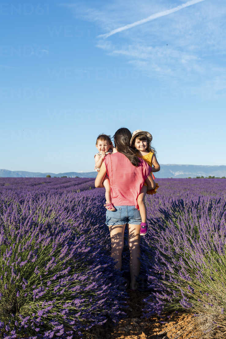 Mother holding two little sisters in a lavender field at afternoon in Valensole, Provence, France - GEMF04697 - Gemma Ferrando/Westend61