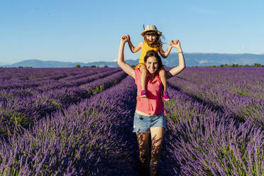 Portrait of mother piggybacking little daughter in vast summer lavender field - GEMF04709