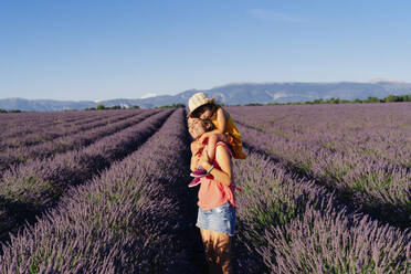 Mother piggybacking little daughter in vast summer lavender field - GEMF04712