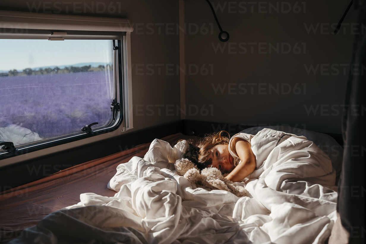 Sweet little girl sleeping in a motorhome with a stuffed rabbit at sunrise next lo lavender fields in Valensole, Provence, France - GEMF04715 - Gemma Ferrando/Westend61