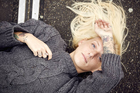 Blond woman lying down at parking lot - UKOF00116