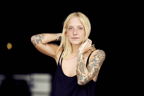 Tattooed woman with hand in hair standing at parking garage - UKOF00125
