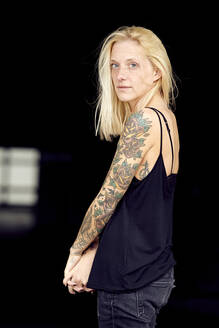 Tattooed woman with hands clasped at parking garage - UKOF00128