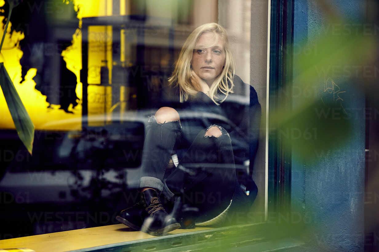 Thoughtful woman sitting on window sill while looking away - UKOF00131 - Uta Konopka/Westend61