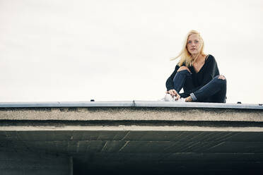Contemplated blond woman sitting on rooftop against clear sky - UKOF00137