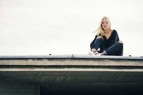 Contemplated blond woman sitting on rooftop - UKOF00137