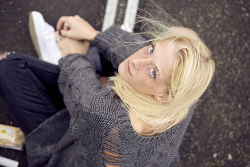 Young woman in sweater sitting with cross-legged at parking garage - UKOF00143