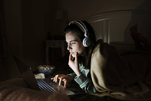 Young woman wearing headphones watching movie on laptop while resting on bed at home - AFVF08208