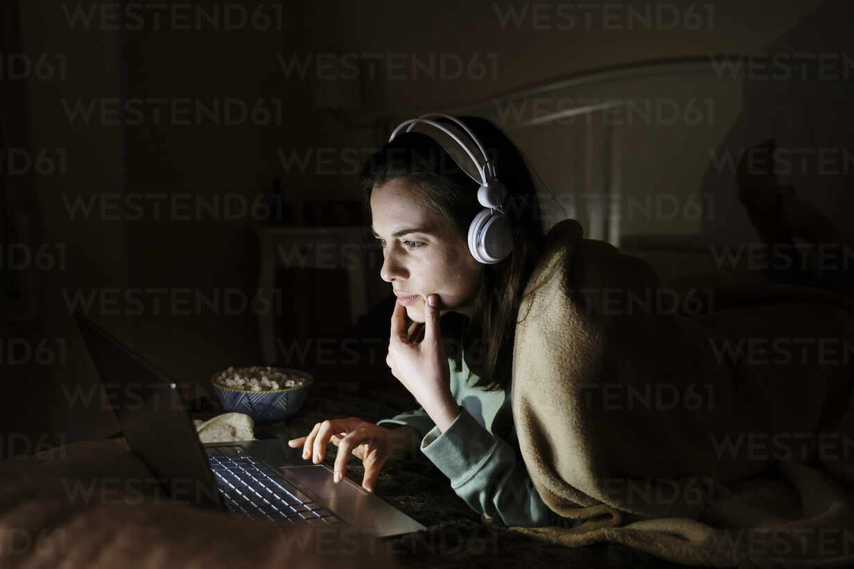 Junge Frau mit Kopfhörern, die einen Film auf dem Laptop schaut, während sie sich zu Hause auf dem Bett ausruht - AFVF08208 - VITTA GALLERY/Westend61