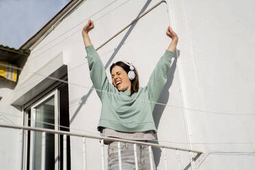 Young woman having fruit smoothie in the morning and waking up, stretching in balcony/terrace - AFVF08217