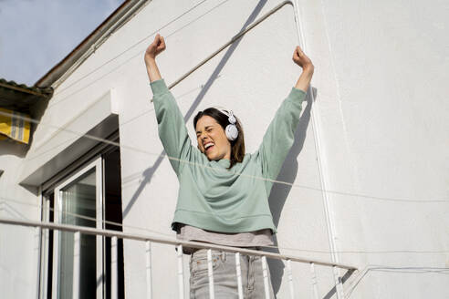 Smiling woman wearing headphones stretching hands while standing in balcony - AFVF08217