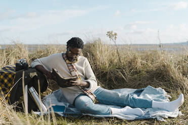 African young man reading book while sitting on blanket at beach against cloudy sky - BOYF01837